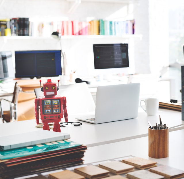 white laptop and red toy robot on white desk
